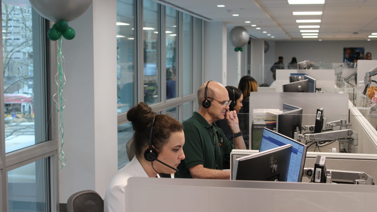 Call center employees at work station by window