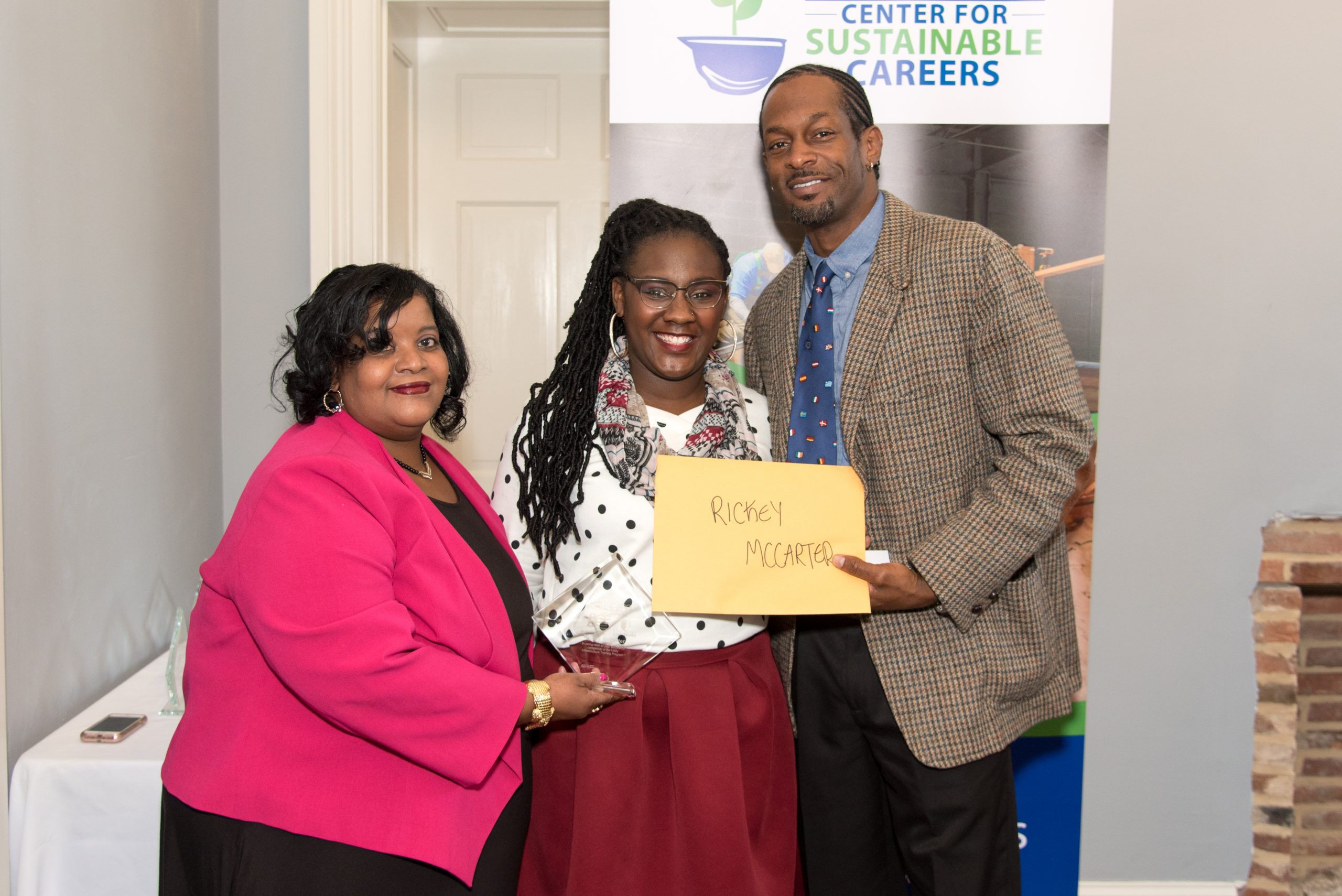 Civic Works staff members Kimberly Armstrong and Vanessa Galloway congratulate Rickey McCarter after graduating from the Workforce Collaborative.